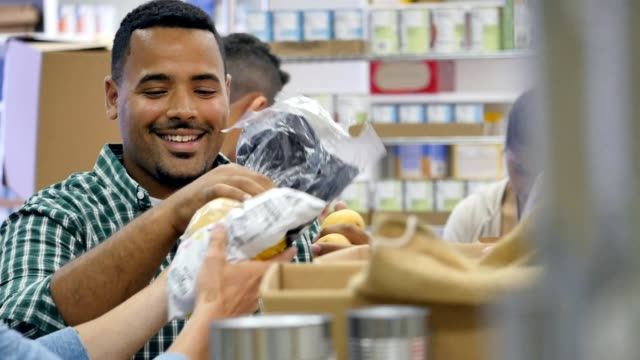 Diverse male friends talk with one another while volunteering in food bank video