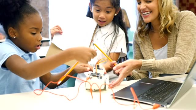 Diverse private STEM elementary schoolgirls are excited as they build a robot video