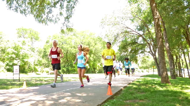 Diverse race competitors running past during marathon or 5k charity race video