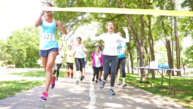 Diverse runners crossing finish line during charity race video
