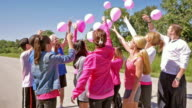 Diverse team of people releasing pink balloons at breast cancer awareness charity race video