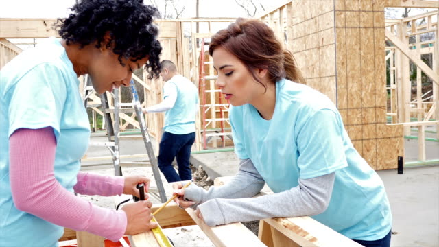 Diverse young women work together to build home for charity video