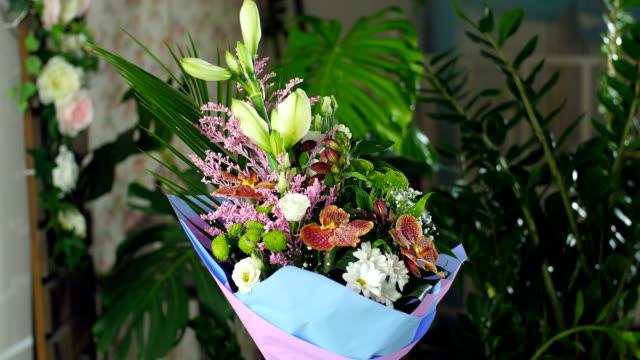 Divine beauty.Flower bouquet in the rays of light, rotation, consists of Orchid vanda, Chrysanthemum bacardi, solidago, Eustoma, Alstroemeria, Santini , gypsophila, Russus , Phoenix robbeli, Amaryllis white, aspidistra video
