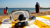 Diving Mask with a Tube for Snorkeling Lying on a Lounger on the Background of the Red Sea Beach in Egypt video