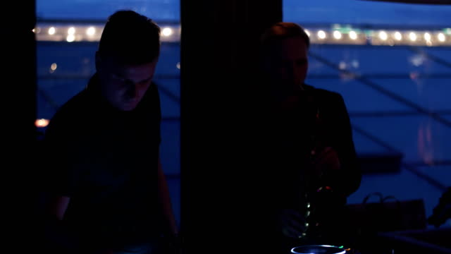 Dj at turntable. Man play saxophone. Party in nightclub. Silhouettes. Musicians video