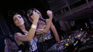 Dj girl and MC girl in mouse ears jump, dance at turntable in club. Slow motion video
