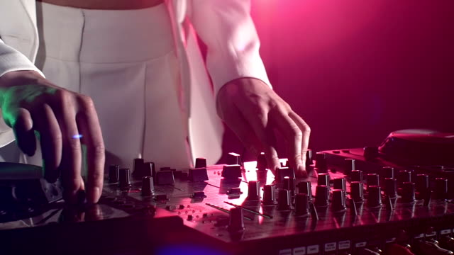 Dj hands on stylish equipment deck, dancing and playing, close up, pink backlight, slow motion video