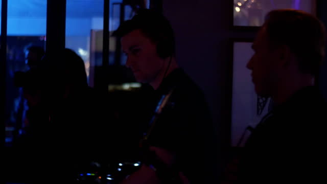 Dj spinning at lighted turntable. Man play saxophone. Party in nightclub. Dance video