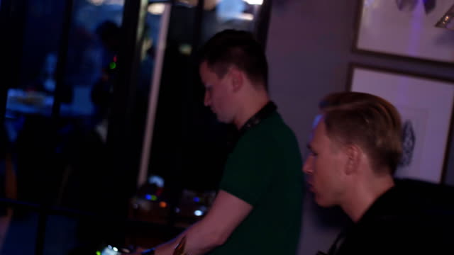 Dj spinning at lighted turntable. Man with saxophone dance. Party in nightclub video
