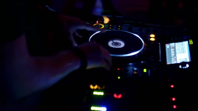 Dj spinning at lighted turntable on party in nightclub. Dance. Mixing. Lights video