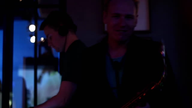 Dj spinning at turntable. Man play saxophone. Party in nightclub. Look in camera video