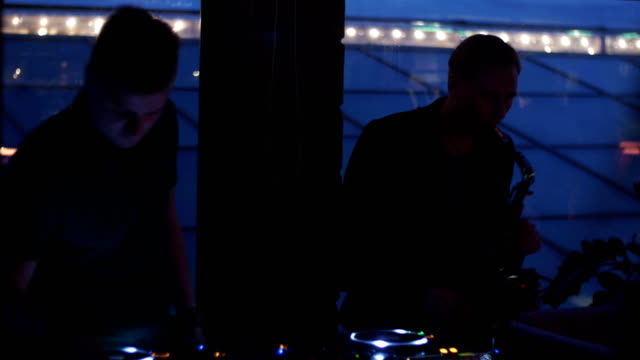 Dj spinning at turntable. Man play saxophone. Party in nightclub. Silhouettes video