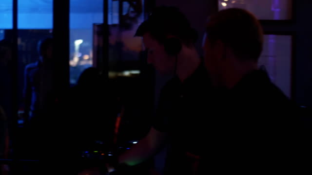Dj spinning at turntable. Man play saxophone. Party in nightclub. Holidays video