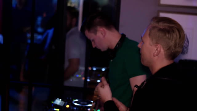 Dj spinning at turntable. Man with saxophone clap in hands. Party in nightclub video