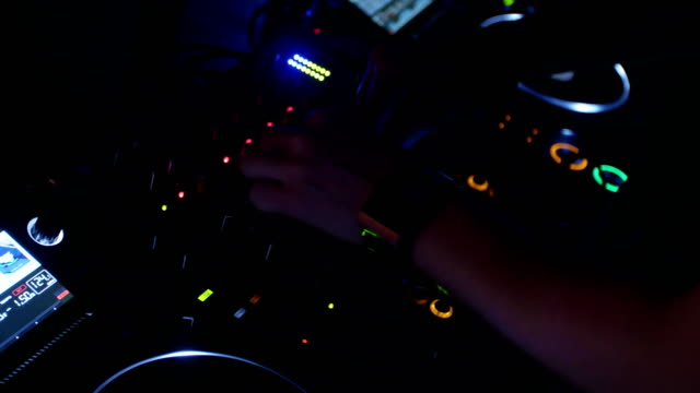 Dj spinning at turntable on party in nightclub. Mixing. Performer. Lights video