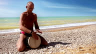 Djembe traditional Drum Player beat rythm on the lonely coast video