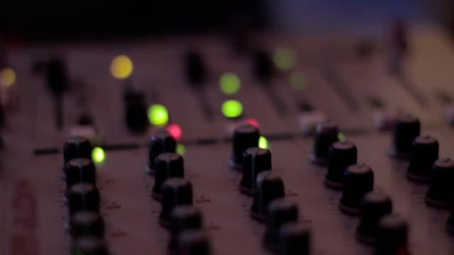 Dj's hands playing disco set, tweaking controls in nightclub video
