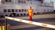 Dock worker in orange uniform walking in the harbor through the barrier video
