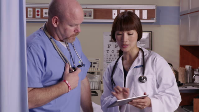 Doctor and male nurse look at tablet video