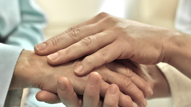 Doctor and patient holding hands video