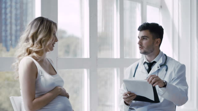 Doctor and pregnant woman in a hospital video