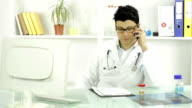 Doctor Arranging Appointment on Phone Writing Down Details video
