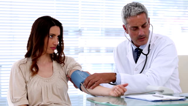 Doctor checking blood pressure of his patient video