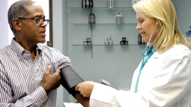 Doctor Checking Male Patient's Blood Pressure video