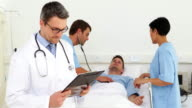 Doctor checking sick patients chart video