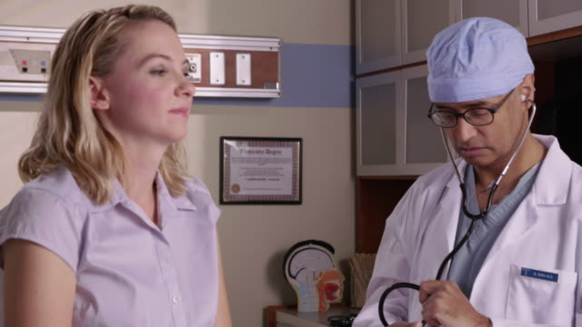 Doctor checking woman's heart with stethoscope video