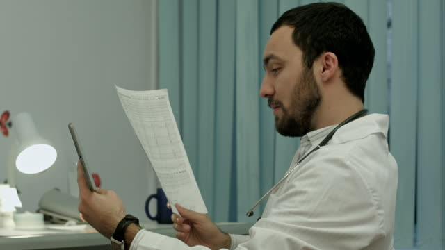 Doctor communicate by video conferention on tablet pc, discuss documents video