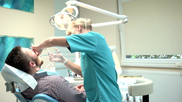 Doctor dentist making an injection of local anesthetic into the gums. Slider. video