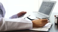 Doctor diagnostic and Writing Prescription on Clipboard with Digital Tablet and examining X-ray image video