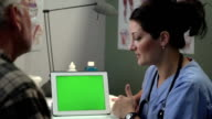 Doctor discussing results with patient on tablet / ipad, green screen video