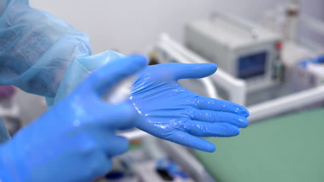 Doctor disinfect latex gloves with spray. medicine and health concept video