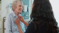 Doctor Examining Senior Female Patient In Surgery video