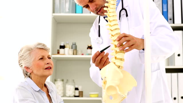 Doctor explaining a spine model to patient video