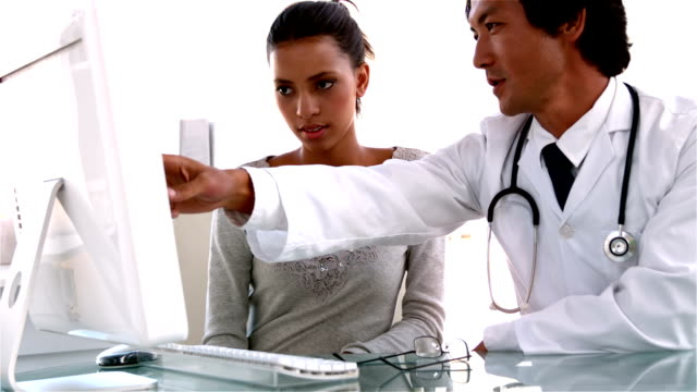Doctor explaining something on computer to patient video