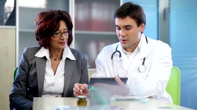 Doctor explaining something to senior woman on digital tablet. video