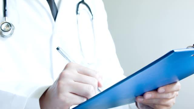 Doctor filling in medical form video