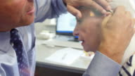 Doctor Fitting Senior Female Patient With Hearing Aid video