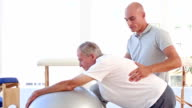 Doctor helping his patient to stretch with exercise ball video