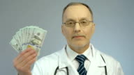 Doctor holding bundle of dollars, paid medicine, expensive health care services video
