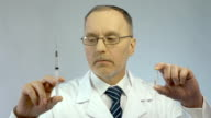 Doctor holding syringe and ampoule, prescribing effective medication to patient video