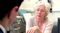 Doctor In Surgery Talking With Worried Senior Female Patient video
