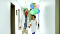 Doctor interacting with patient while walking in corridor video