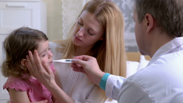 Doctor is measure the temperature of little girl. video