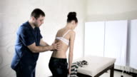 Doctor manual therapist checks scoliosis spine girl patient video