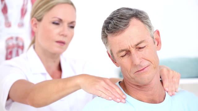 Doctor massaging her patients shoulders video