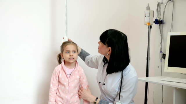 doctor measures growth of patient, child at doctor's appointment, nurse works in hospital, sick child in children's clinic video